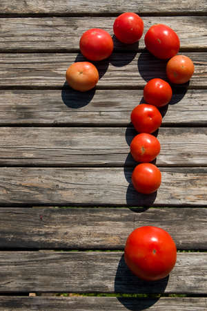 eating questions: Tomatoes in the form of a sign on a question on wooden table Stock Photo