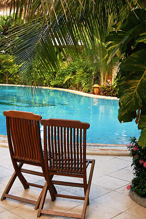 chillout: two wooden chairs at the pool side