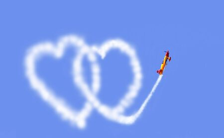 an aeroplane drawing hearts in the sky                                 photo
