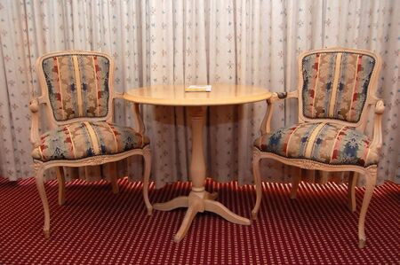 classy interior- two chairs and table placed against drawn curtains photo