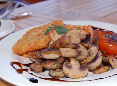 close up of a plate with hash brown , mushrooms and baked beans                                   photo