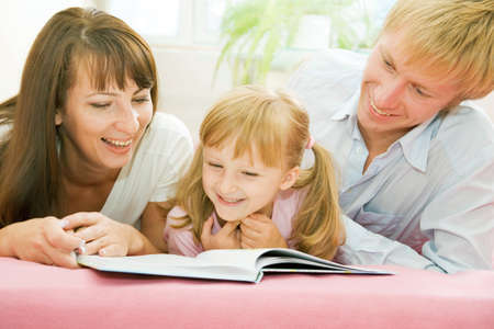 togther: Portrait of happy family reading the book together at home Stock Photo