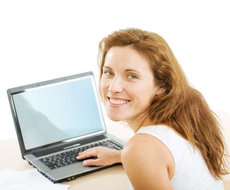 Smiling businesswoman looking at camera while touching keys of laptop near by photo