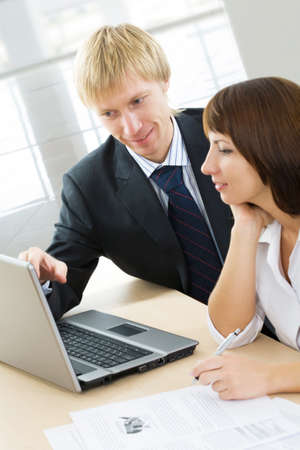 A man points at a screen of a laptop and a woman looks at it  photo