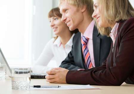 Image of glass of water, pen and paper with row of businesspeople at background Stock Photo - 4162149