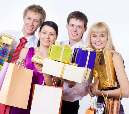 Four young people hold gift boxes and bags photo