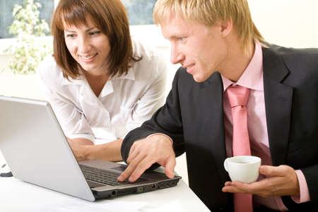 Image of successful businessman touching key of laptop with pretty female near by photo