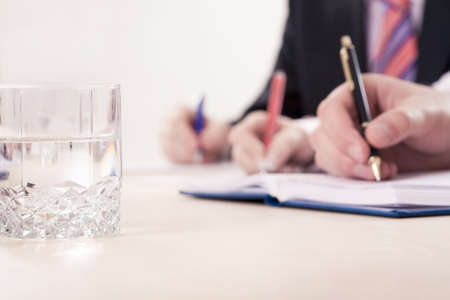 Hands writing notes, focus is on the glass with water Stock Photo - 4231214