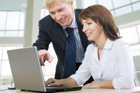 A boss and a secretary, a secretary uses laptop Stock Photo