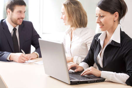 operates a laptop and her colleagues hold discussions photo