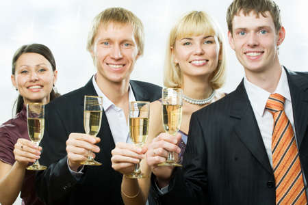 Two men and two women stay in line, hold tumblers with champagne photo