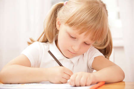 kids writing: Portrait of serious girl writing something in copybook