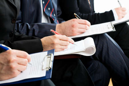 filling in: Row of hands filling in a form