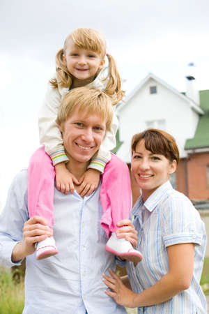 Image of small girl sitting on the father�s shoulders and woman near by Stock Photo - 4750143
