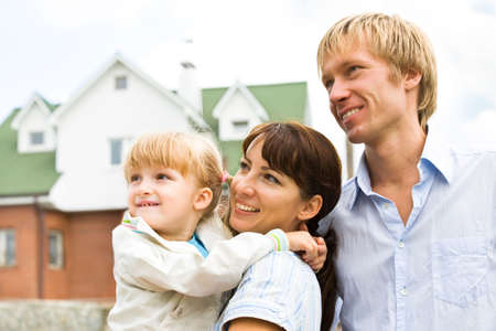 familia abrazo: Retrato de mujer con la hija muy cerca de el hombre en el fondo de casa