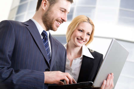 Two colleagues using lap-top near an office centre Stock Photo - 4765449