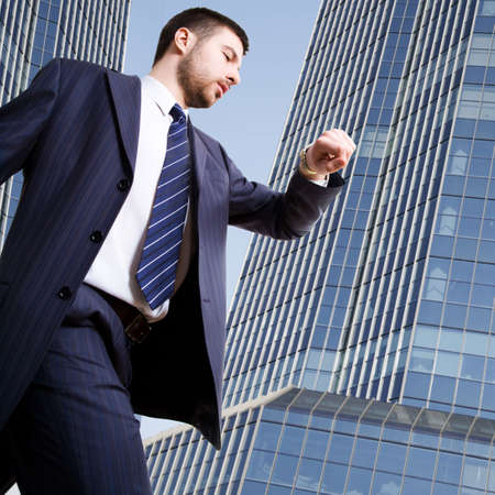 A hurrying up businessman looking at his wrist watch Stock Photo