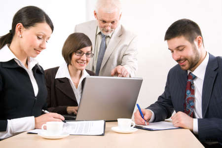 Four businesspeople discussing computer work photo