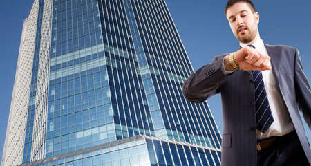 A businessman looking at wrist  watch against a  skyscraper photo