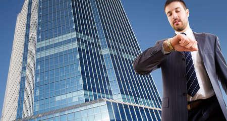 uomo alto: Un uomo d'affari in cerca di orologio da polso contro un grattacielo