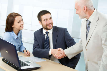 Two businessman shaking hands in a modern office photo