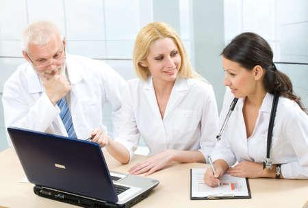Three medicine workers discuss computer work photo