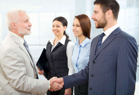 politeness: Business people shaking hands in a modern office centre