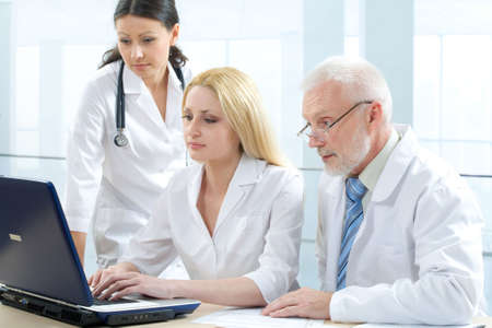 Three medicine workers looking at monitor photo