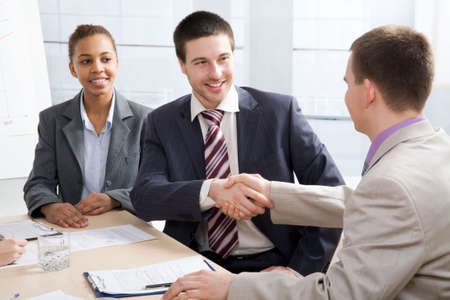 politeness: Businessmen joining hands in an office