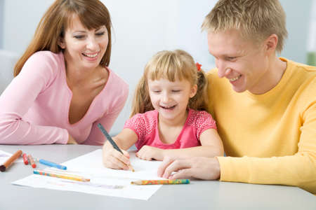 Portrait of little girl painting something and her father and mother looking at this photo