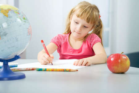 Portrait of the little girl drawing houses photo