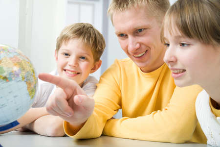 A father shows his family countries on a globe Stock Photo - 6866600