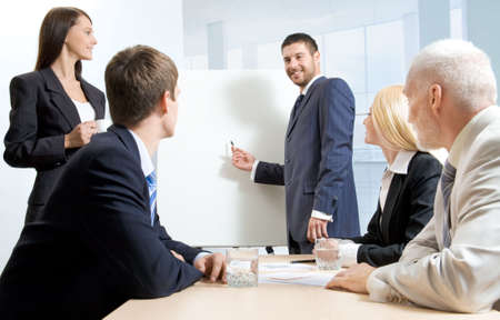 flipchart: A businessman making a report and four people listening to him Stock Photo
