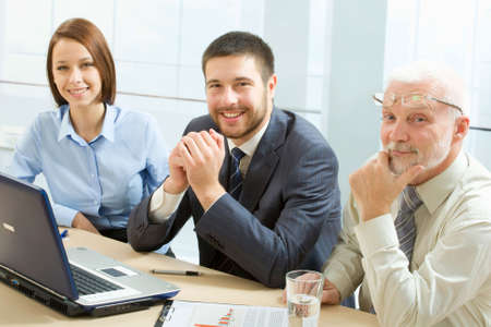 A group of business people sitting at table, looking at camera Stock Photo - 6866570