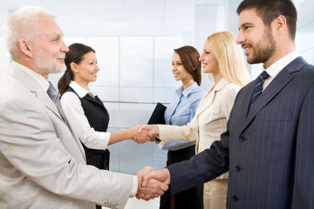 delegation: Business people shaking hands in a modern office Stock Photo