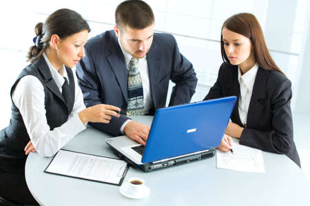 Three  business people working with lap-top photo