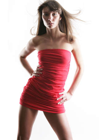 The sexual girl in a red dress on a white background photo