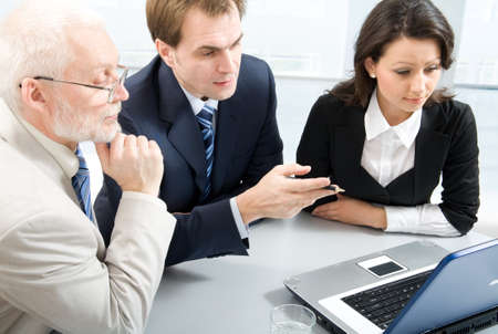 employees working: Three business people working with lap-top