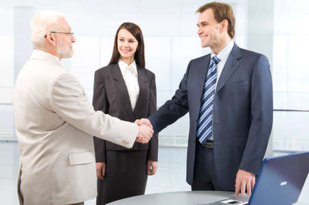 Businesspeople shaking hands in a modern office  photo