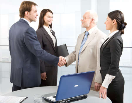 old office: Group of four business people shaking hands in an office Stock Photo
