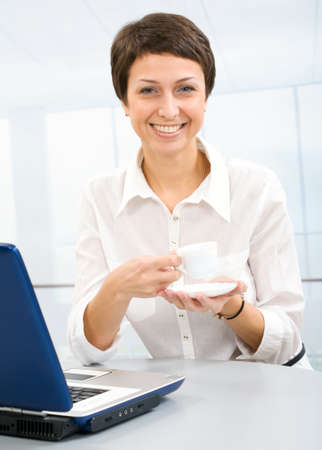 The beautiful business woman with a coffee cup photo