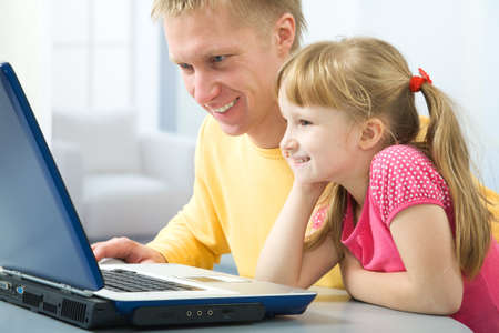 The father and his daughter use the laptop photo