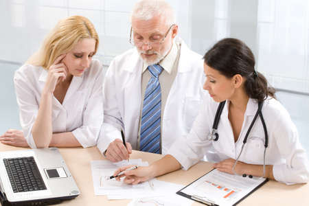 Three  physicians discuss the results of treatment photo