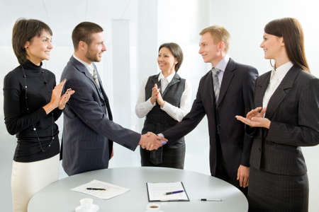 civility: Business colleagues shaking hands and applauding