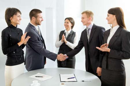 desired: Ejecutivos de estrechar la mano y aplaudiendo Foto de archivo