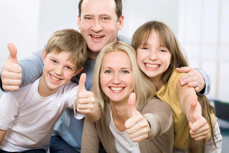 family looking up: Cheerful family of four with their thumbs up