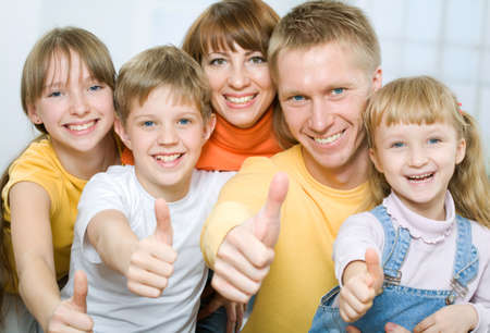 Cheerful family of five with their thumbs up photo
