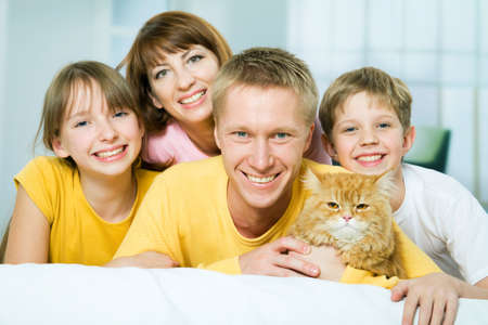 Portrait of a happy family with a house cat looking at camera   photo