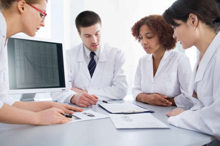 nurse computer: Group of young doctors discuss work Stock Photo