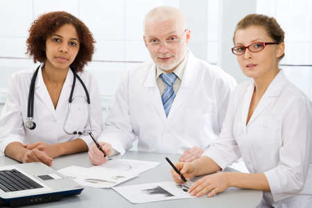 Group of doctors sit on a workplace and look at the camera photo